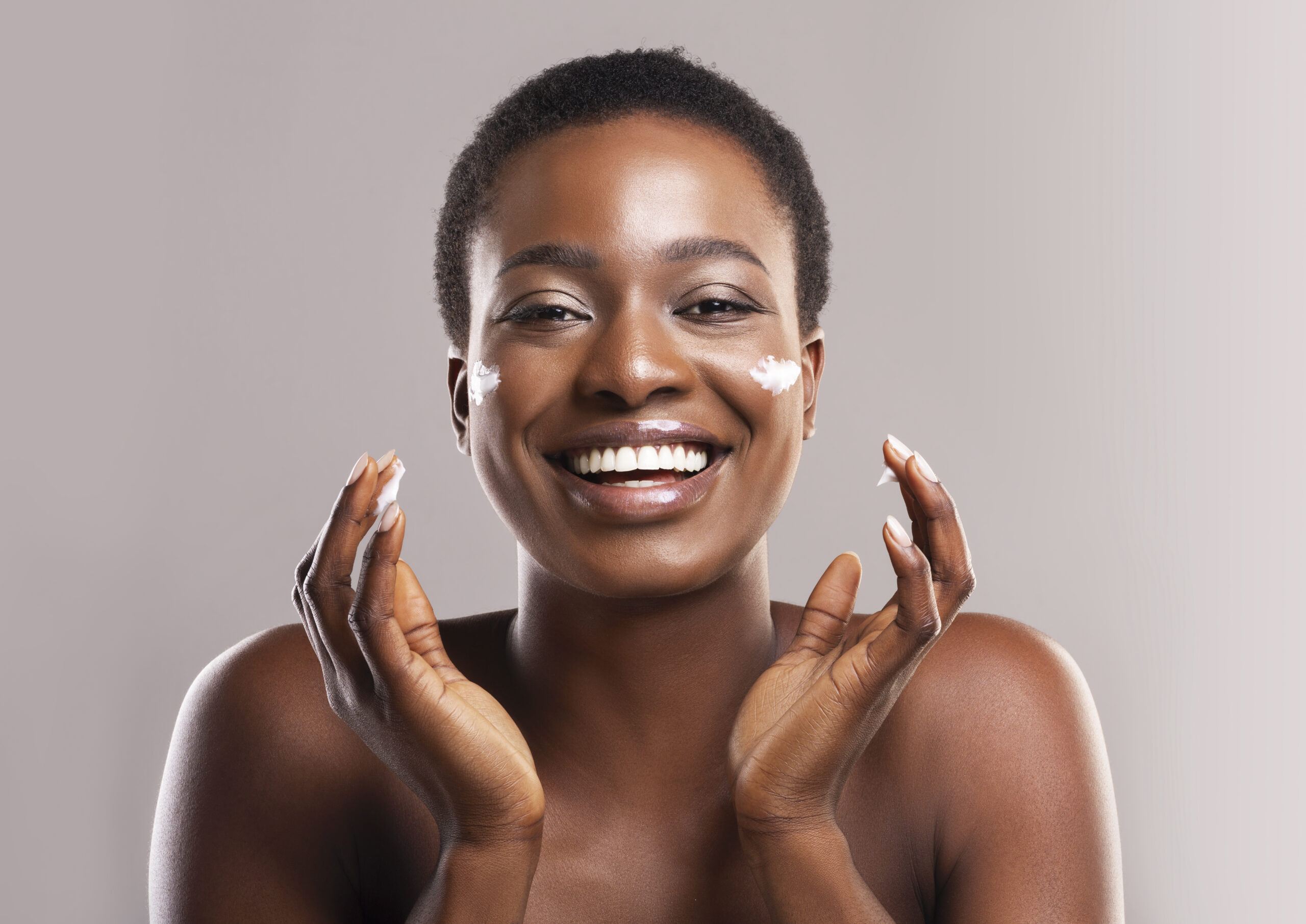 woman applying skincare to her face